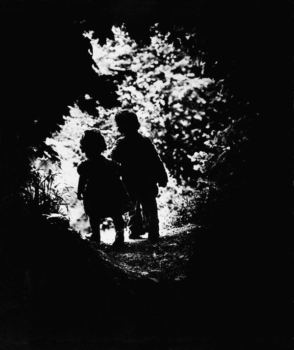 LIFE photographer W. Eugene Smith's children walk into a clearing.