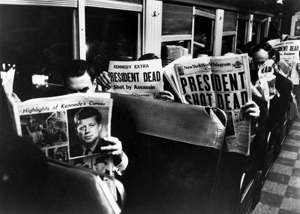 Commuters read about JFK assassination. Photo by LIFE photographer Carl Mydans.